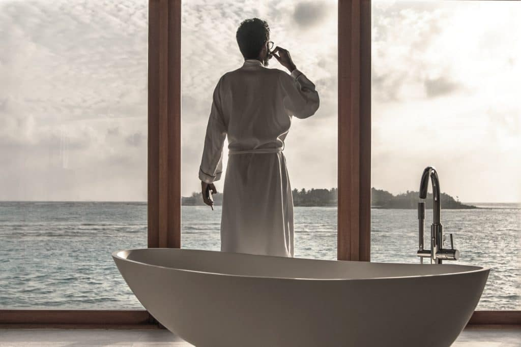 image of man standing next to bath filled with hot water