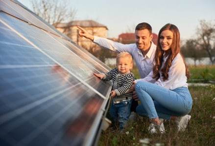 image of family looking at ground installed solar panels