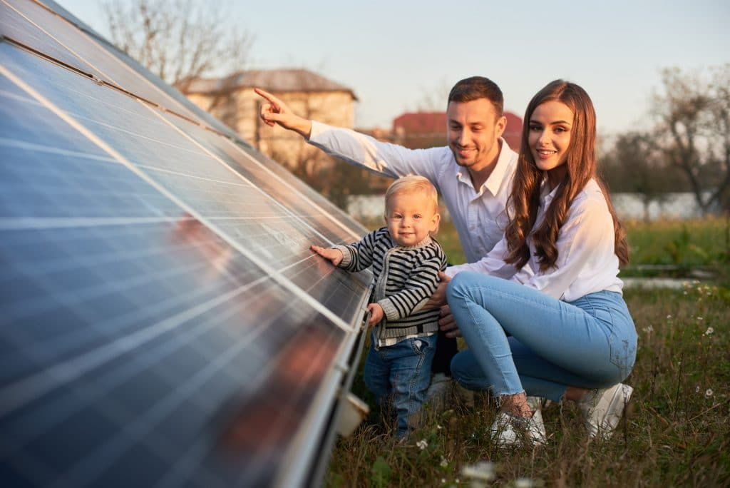 image of father showing his family a solar panel array