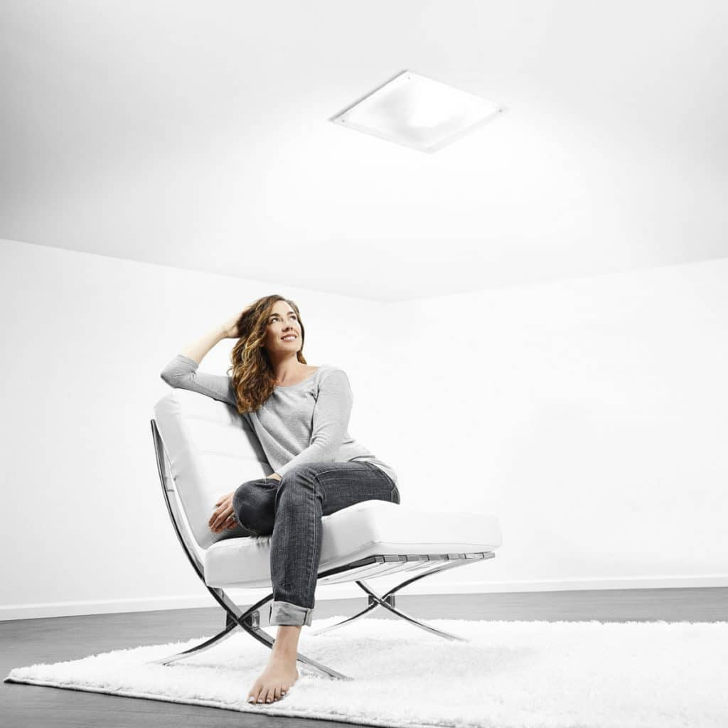 Image of woman sitting underneath a solar skylight